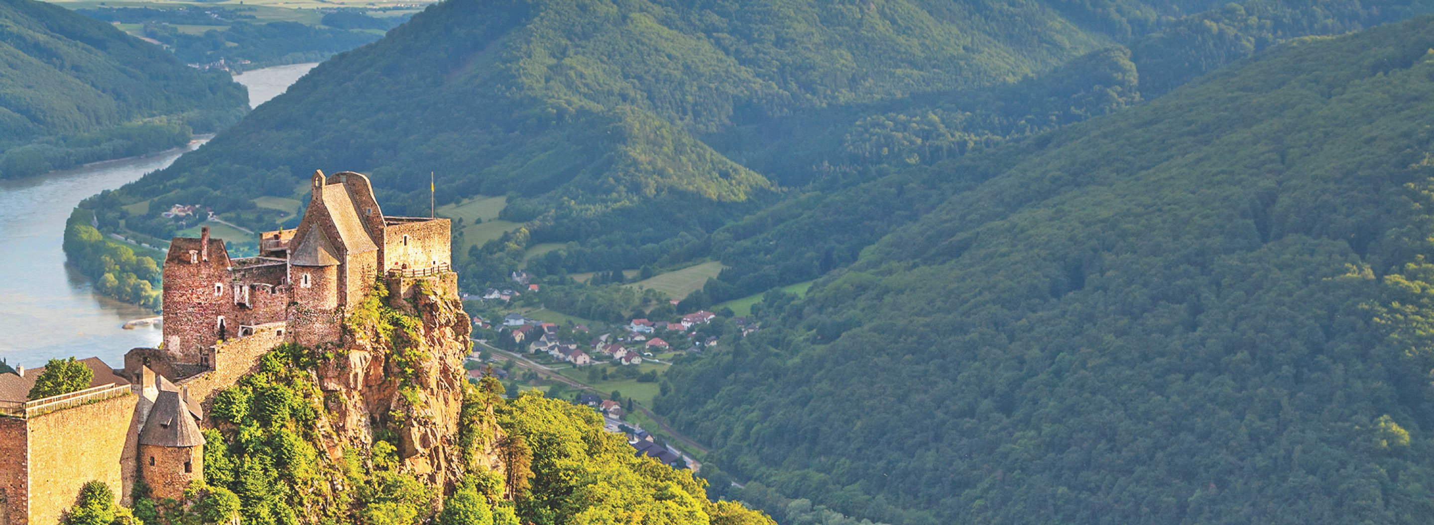 Image of a European castle perched on a grand mountainside.